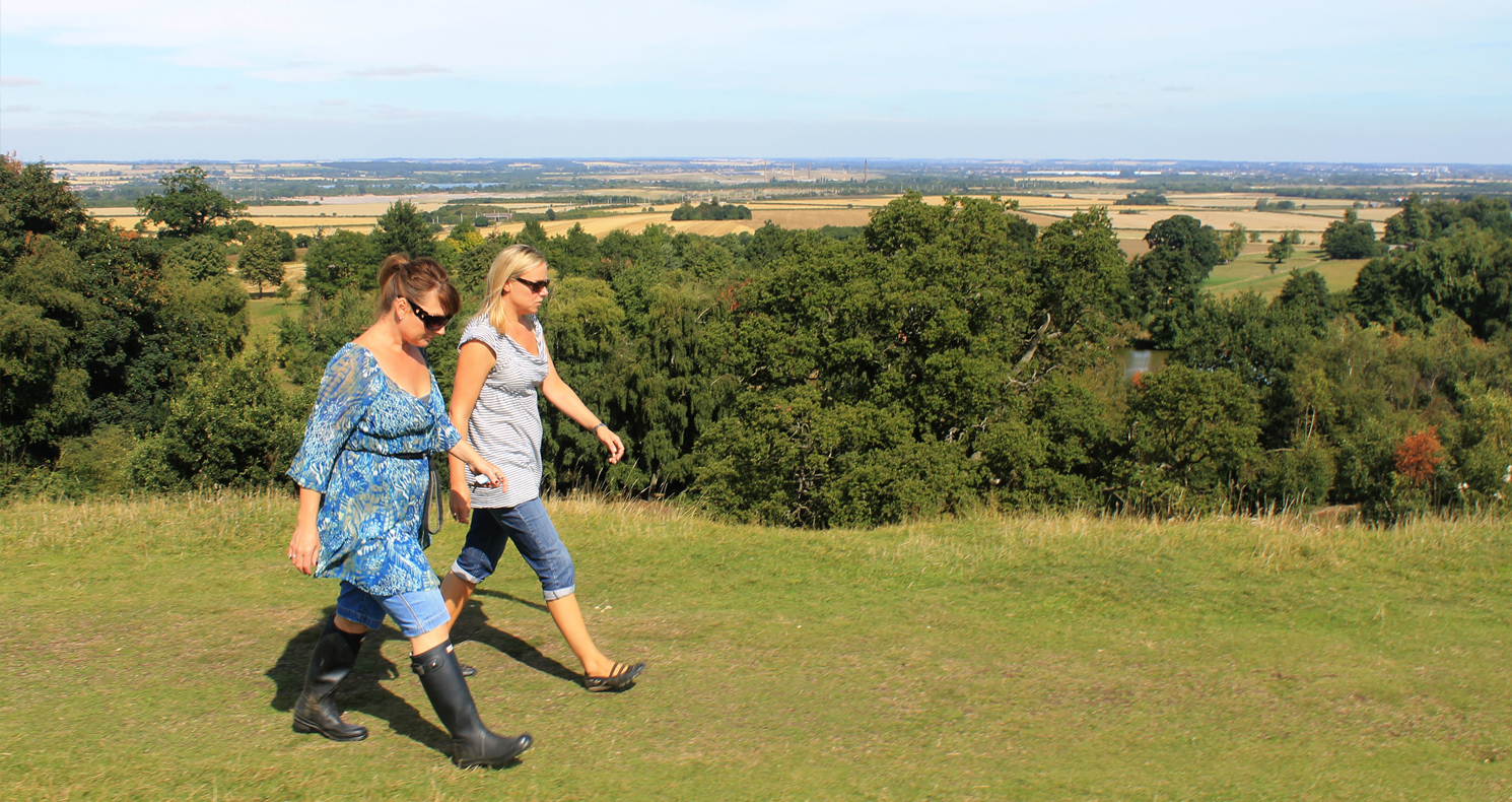 Two women walk through Ampthill Park