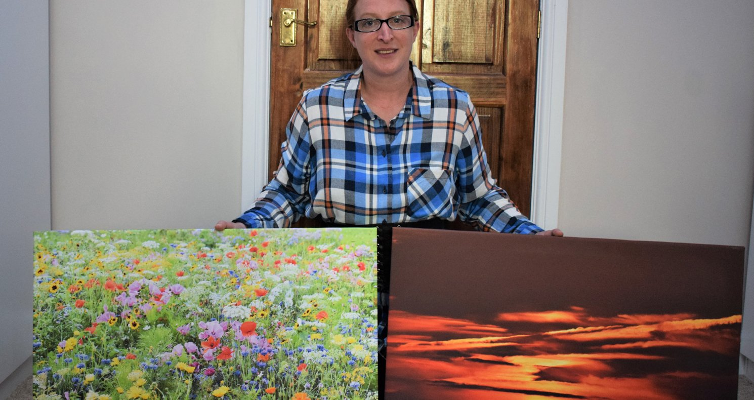 Lady holds two canvases showing photos she