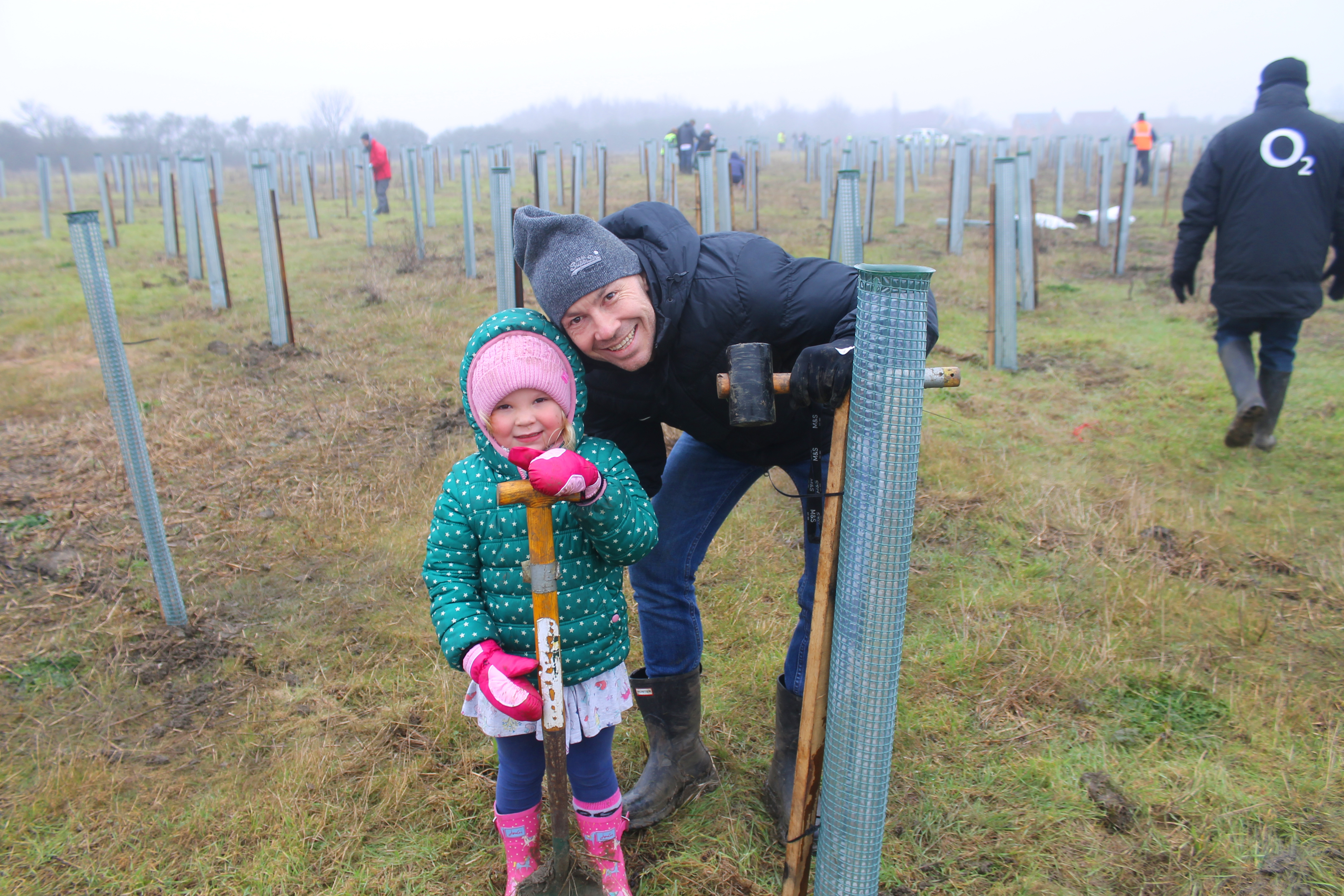 A child and her father plant a tree in winter