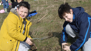Two boys plant a tree at Waypost Wood
