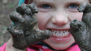 A child with muddy hands in the Park