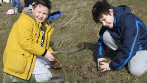 Two school children plant trees at Waypost Wood