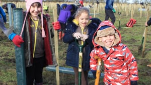 Three kids planting trees at Waypost Wood