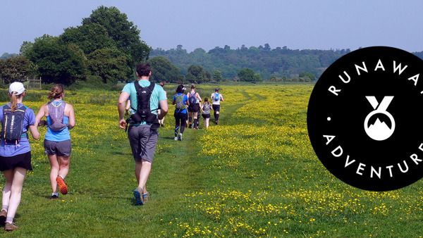 Runners in a green field, with the Runaway Adventures logo