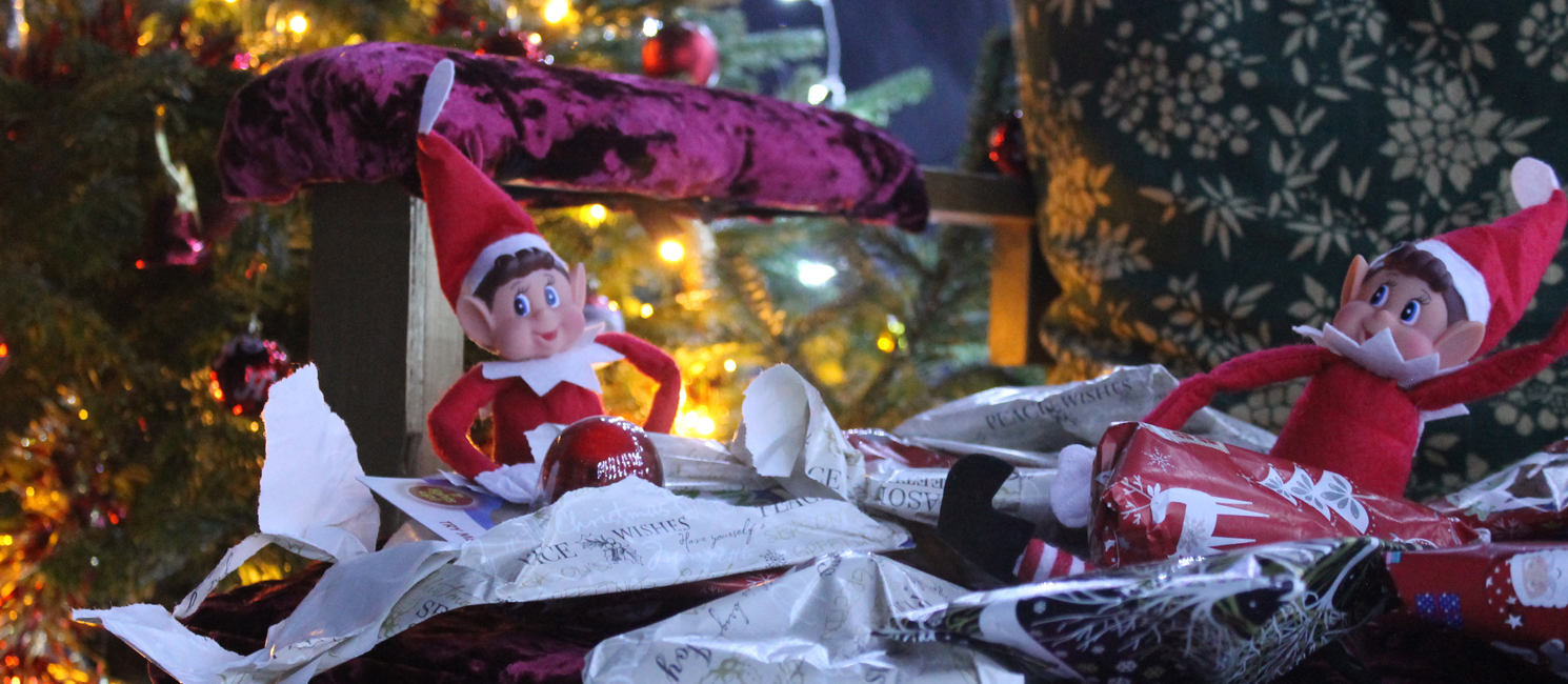 Two elves open presents in a Christmas grotto
