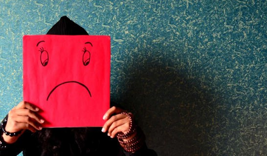 Sad face drawn on a red board, held in front of someones face.