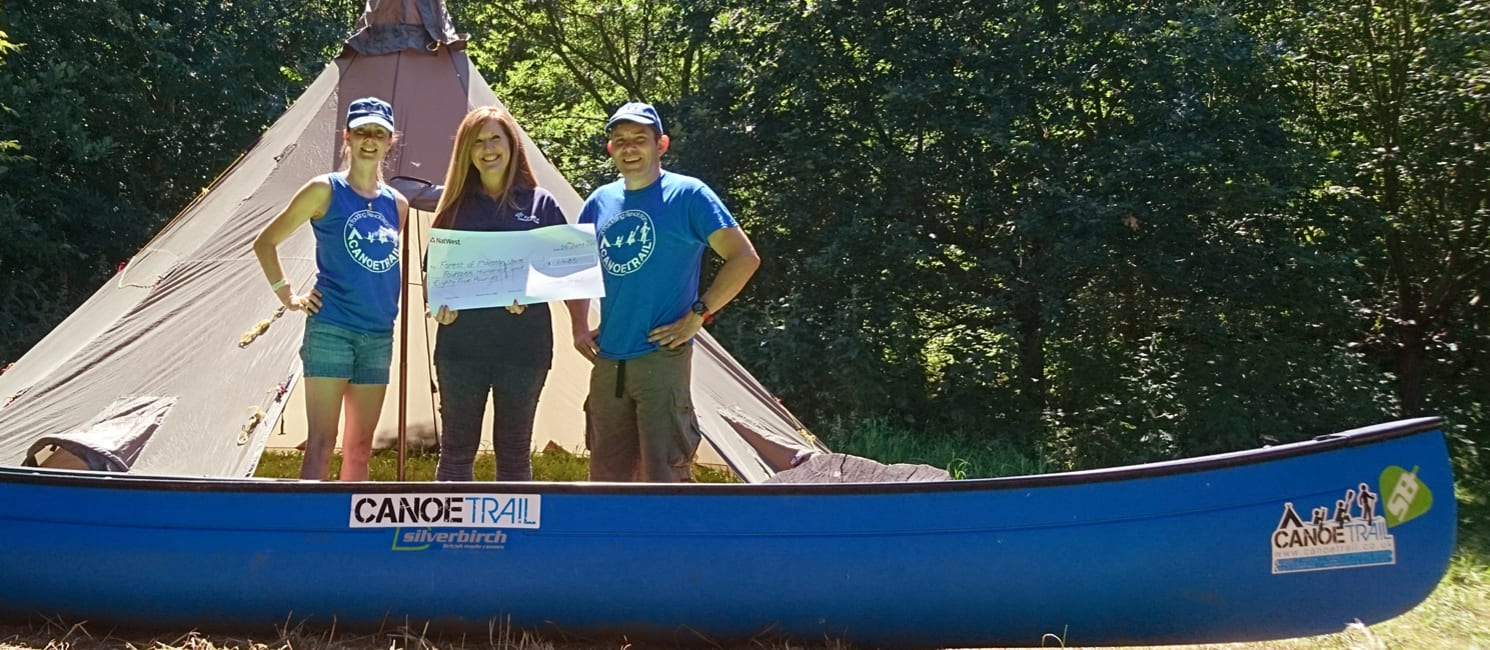 Richard and Ashley from Canoe Trail present our fundraiser with a cheque, in a kayak