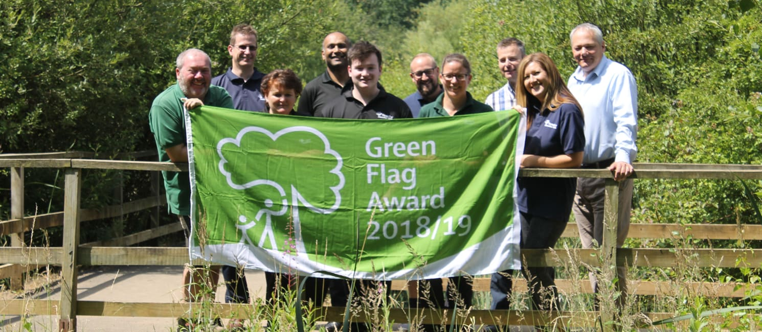 Staff from the Forest of Marston Vale holding the green flag for 2018/19 in the Park